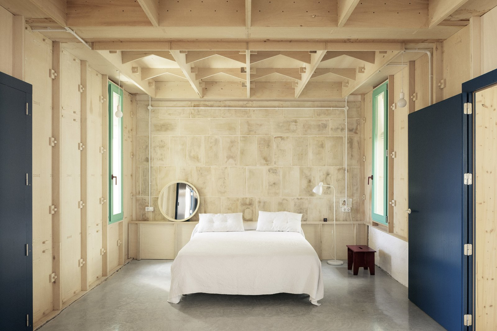 Bedroom, Bed, Concrete, Floor, Shelves, Night Stands, Lamps, and Pendant The master bedroom.  Best Bedroom Shelves Pendant Concrete Photos from A Luminous Plywood Addition Crowns This Mallorca Townhouse