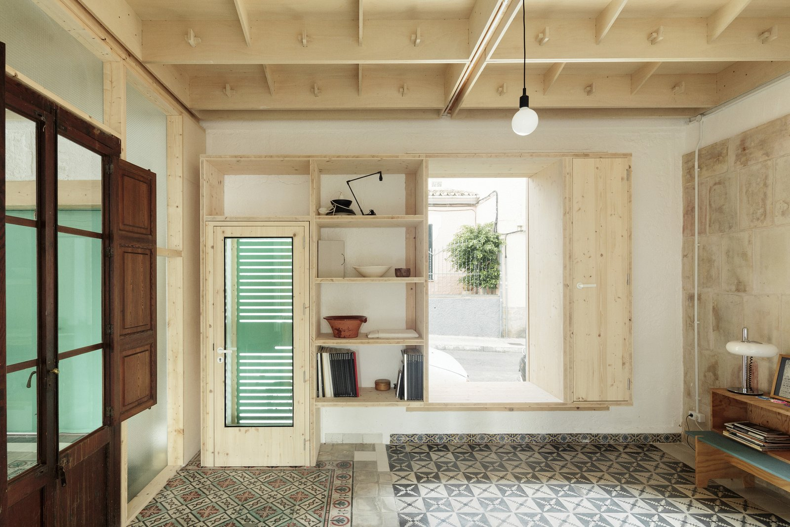 Living, Ceramic Tile, Table, Shelves, Storage, Lamps, Pendant, and Console Tables Light from outdoors streams into one of the atmospheric interior spaces.  Best Living Ceramic Tile Console Tables Photos from A Luminous Plywood Addition Crowns This Mallorca Townhouse