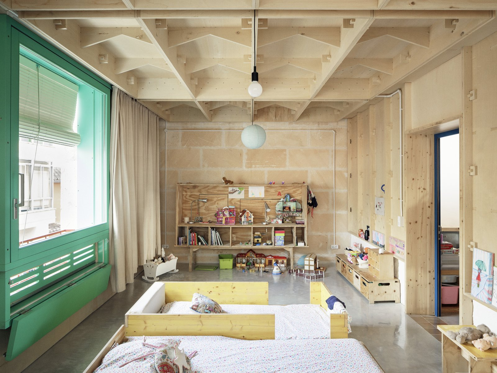 Kids Room, Toddler Age, Bedroom Room Type, Shelves, Bed, Bookcase, Neutral Gender, Concrete Floor, and Storage The children's bedroom and play area.  Photo 15 of 19 in A Luminous Plywood Addition Crowns This Mallorca Townhouse