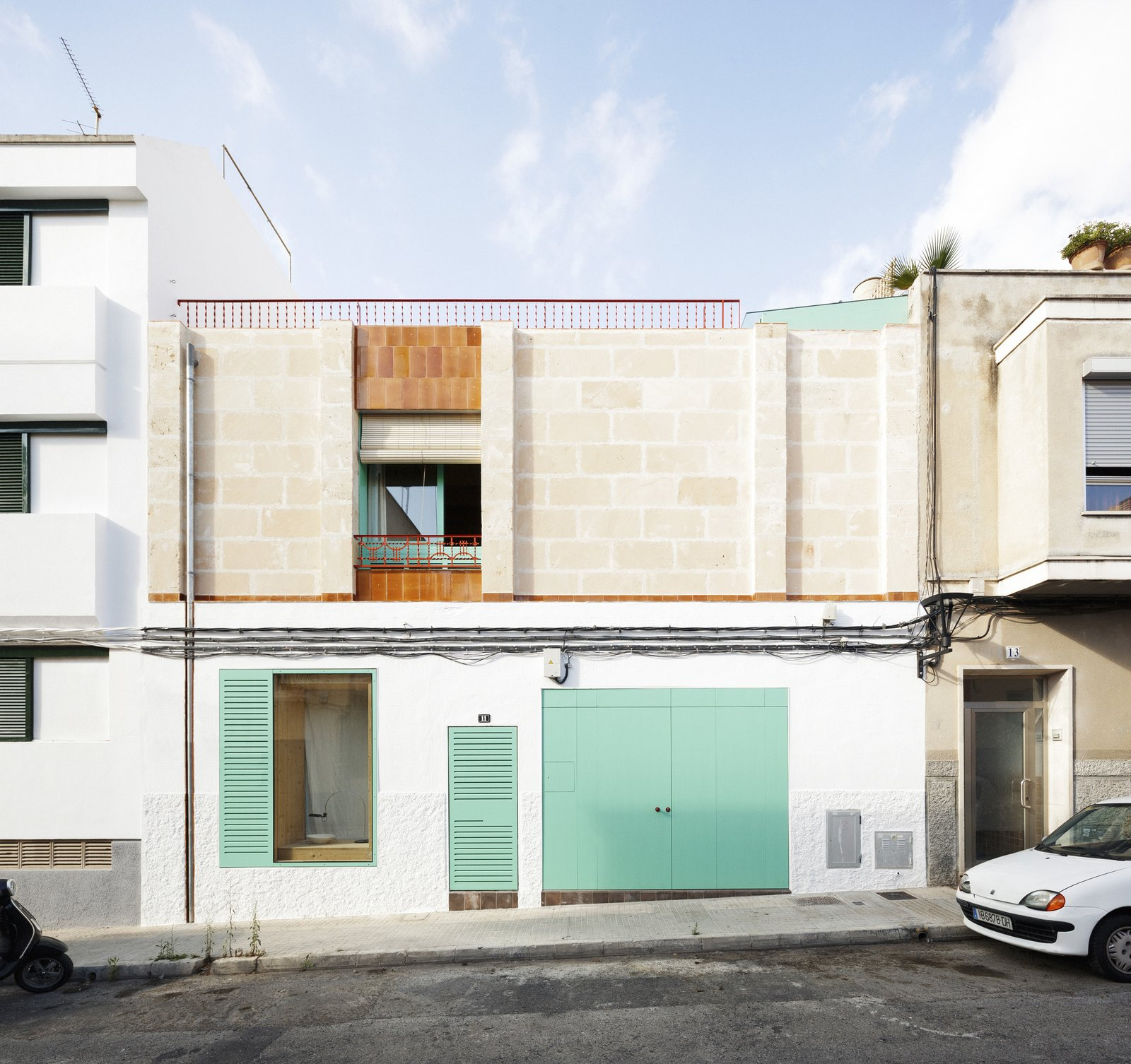 Exterior, House, Brick, Flat, and Stucco A street view of City House reveals its cheerful, teal accents.  Exterior Stucco Brick Photos from A Luminous Plywood Addition Crowns This Mallorca Townhouse
