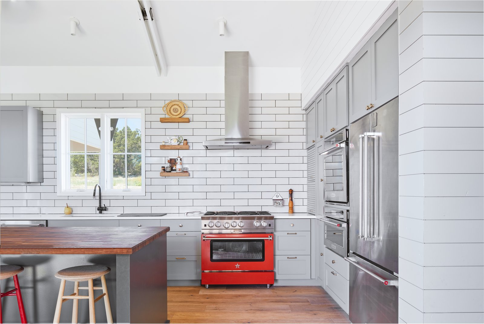 Kitchen, Wall Oven, Refrigerator, Wood, Range Hood, Range, Microwave, Quartzite, Wood, Medium Hardwood, Ceiling, Undermount, and Subway Tile The splash of red repeats itself in the kitchen oven.  Best Kitchen Wood Quartzite Range Undermount Photos from Interior Spaces