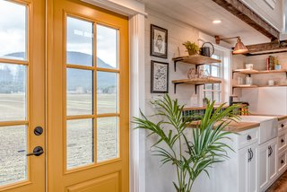 The home boasts a cheery yellow entrance door.