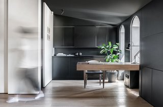 A sparse wooden desk and ample black cabinetry are elements that can be used as modern home office ideas. Vibrant natural light floods the room with light despite the dark background in this expansive modern home office in a heritage apartment in Kiev.