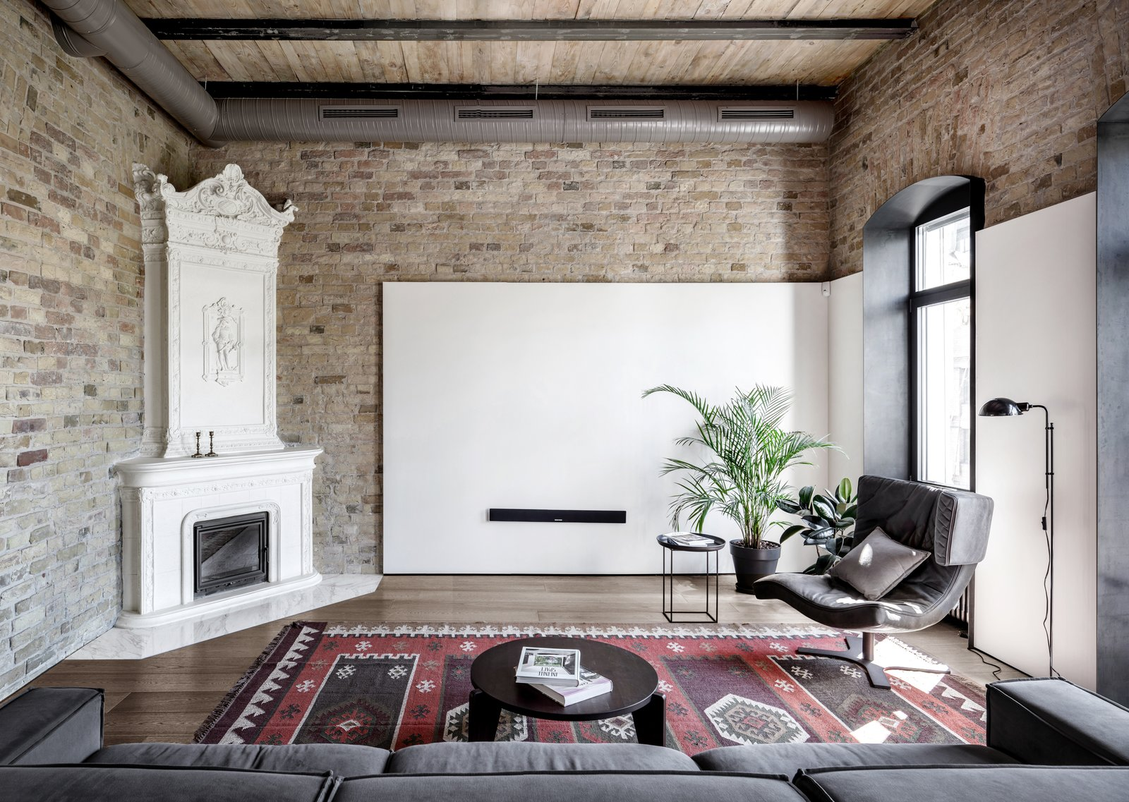 Living, Sofa, Corner, Rug, Medium Hardwood, Floor, Chair, Lamps, Standard Layout, Coffee Tables, End Tables, and Gas Burning Jaipur Zinfandel carpet.  Living Medium Hardwood Standard Layout Corner Photos from A Monochromatic Palette Unifies Old and New in This Ukrainian Bachelor Pad