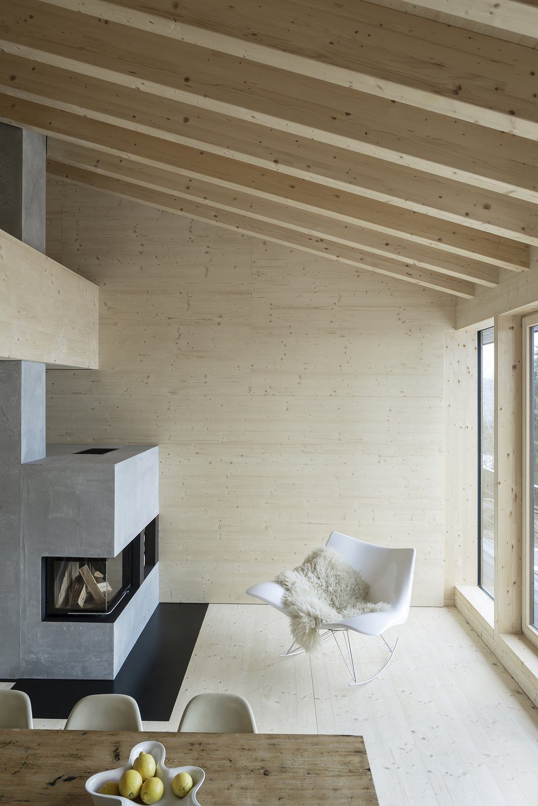 Living, Chair, Table, Standard Layout, Light Hardwood, and Wood Burning In the living area is a modern, minimalistic concrete fireplace.    Best Living Table Wood Burning Photos from Charred Wood and Concrete Unite to Form a Chalet–Inspired Home
