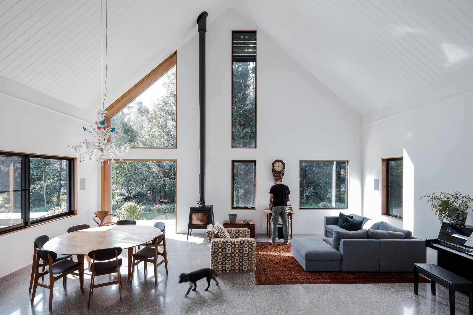 Living, Concrete, Pendant, Wood Burning, Chair, Table, Ottomans, Sectional, and Rug The dining table and chairs were designed by Tim Sharpe.  Best Living Pendant Ottomans Wood Burning Photos from Two Barn-Like Volumes Make Up This Low-Maintenance Australian Home