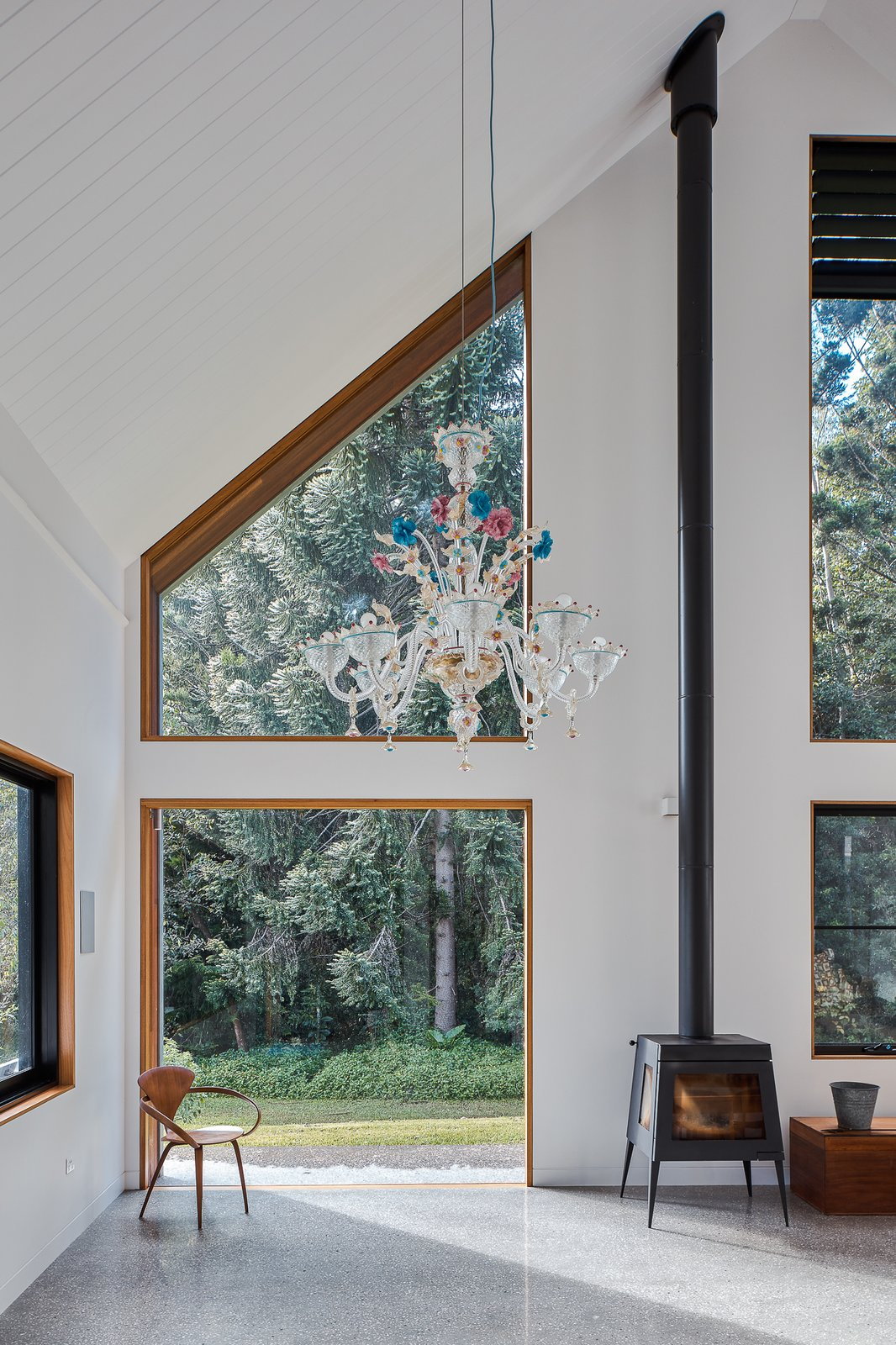 Living Room, Pendant Lighting, Wood Burning Fireplace, Concrete Floor, Chair, and End Tables Chandelier commissioned by Rani Blancpain from Murano, Italy.  Photo 12 of 19 in Two Barn-Like Volumes Make Up This Low-Maintenance Australian Home