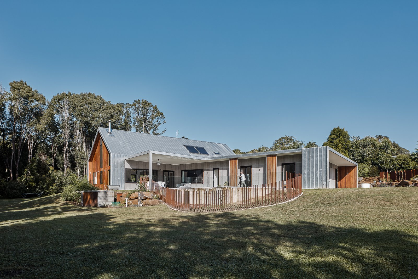 Exterior, House, Metal, Gable, Wood, Metal, Concrete, and Flat Tim Sharpe and Rani Blancpain wanted a home that would allow them to enjoy an indoor-outdoor lifestyle.  Best Exterior Metal Wood Gable Concrete Photos from Two Barn-Like Volumes Make Up This Low-Maintenance Australian Home