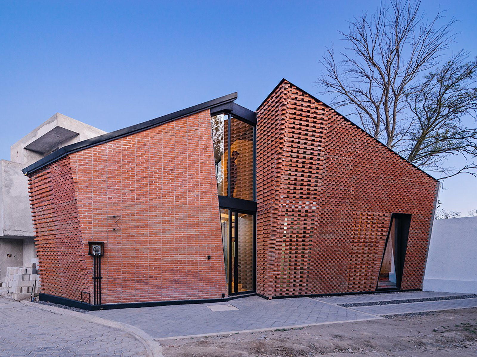 Exterior, Brick Siding Material, House Building Type, Gable RoofLine, and Metal Roof Material The traditional bricklaying technique enabled the second-level interior space to become larger.    Photo 2 of 14 in Extruded Red Bricks Create a Gorgeous, Geometric Mexican Home