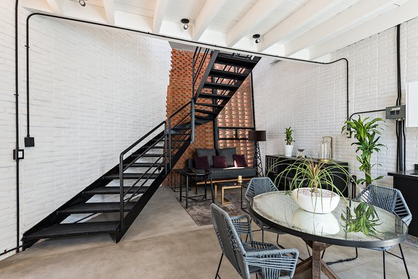 A sculptural metal staircase leads up from the open common area to the mezzanine bedroom.