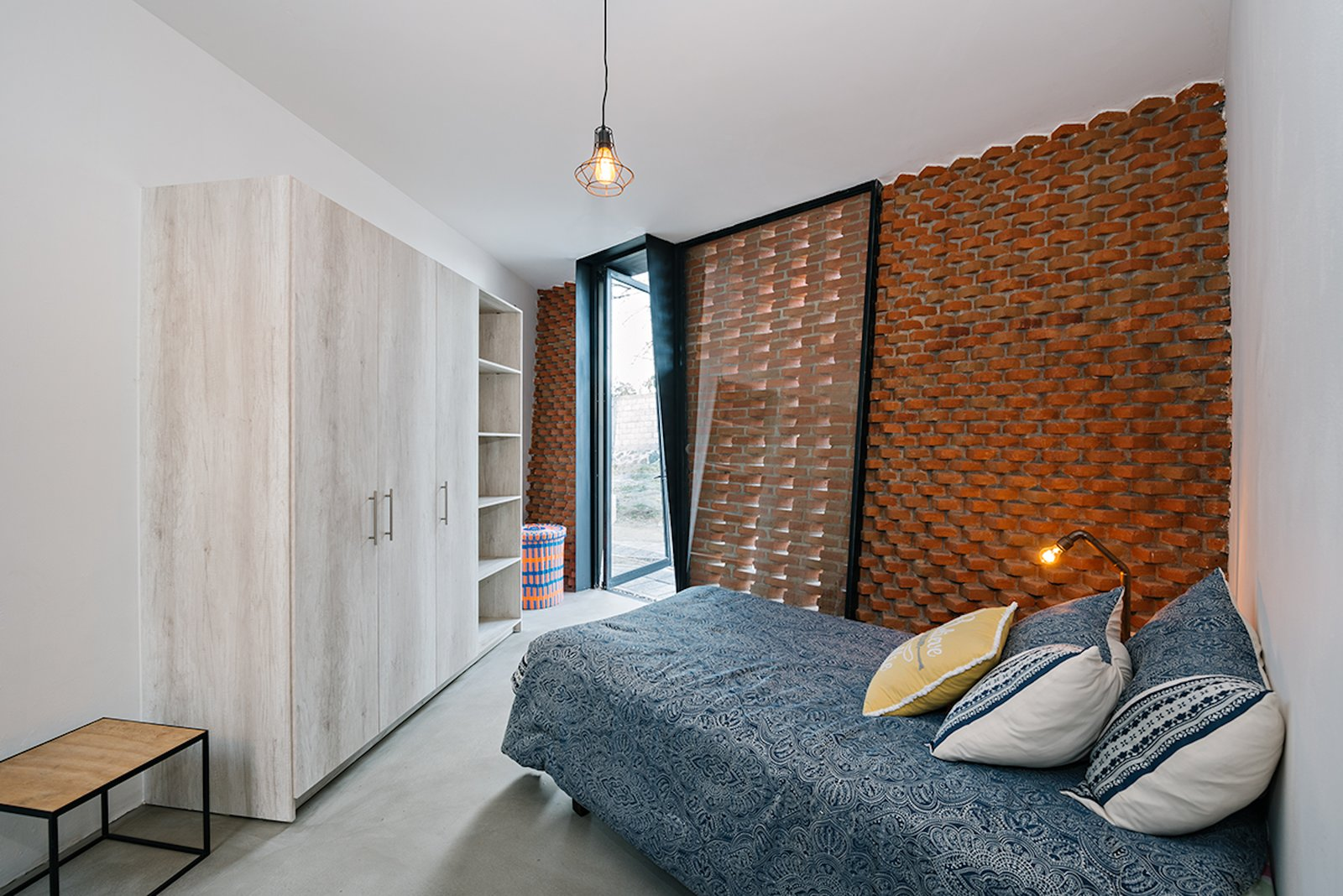 Bedroom, Pendant Lighting, Concrete Floor, and Bed A second bedroom, along with a bathroom and laundry room, are set around an interior patio that is connected to the master bedroom.    Photo 9 of 14 in Extruded Red Bricks Create a Gorgeous, Geometric Mexican Home