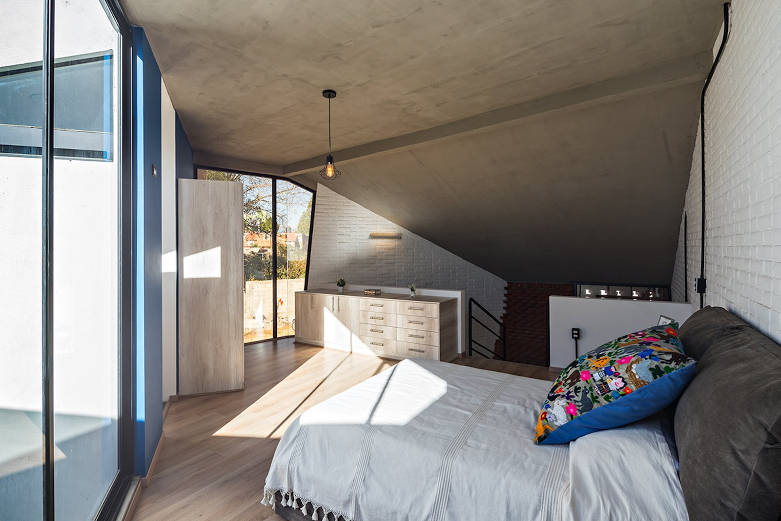 Bedroom, Storage, Pendant Lighting, Light Hardwood Floor, Wardrobe, and Bed A look at the master bedroom located on the mezzanine level.     Photo 8 of 14 in Extruded Red Bricks Create a Gorgeous, Geometric Mexican Home