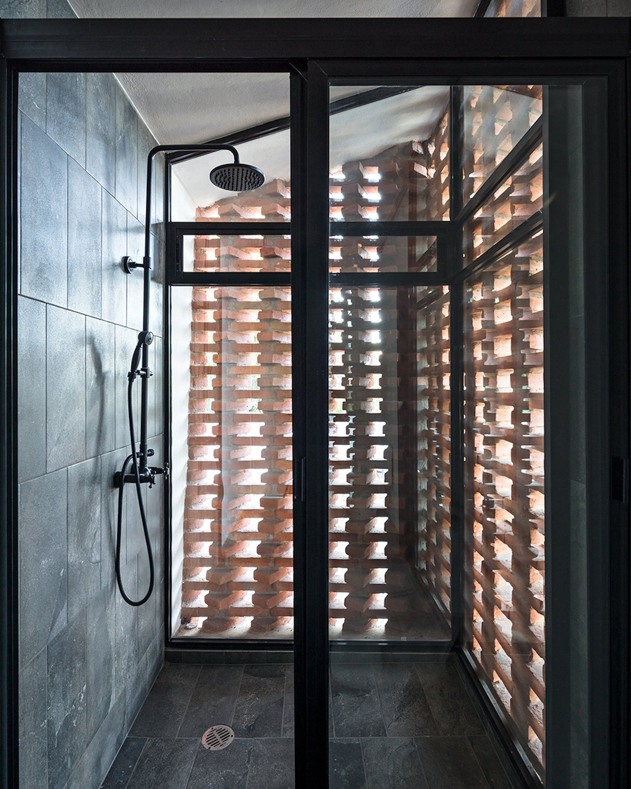Bath Room, Slate Floor, and Enclosed Shower Sunlight enters the shower area through the gaps between the bricks.    Photo 11 of 14 in Extruded Red Bricks Create a Gorgeous, Geometric Mexican Home