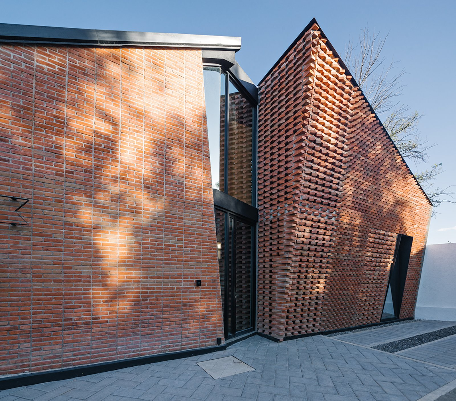 Exterior, House Building Type, Metal Roof Material, Gable RoofLine, and Brick Siding Material The gaps between the courses also allow the brick wall to double as a window, framing views and drawing in more light and air.     Photo 3 of 14 in Extruded Red Bricks Create a Gorgeous, Geometric Mexican Home