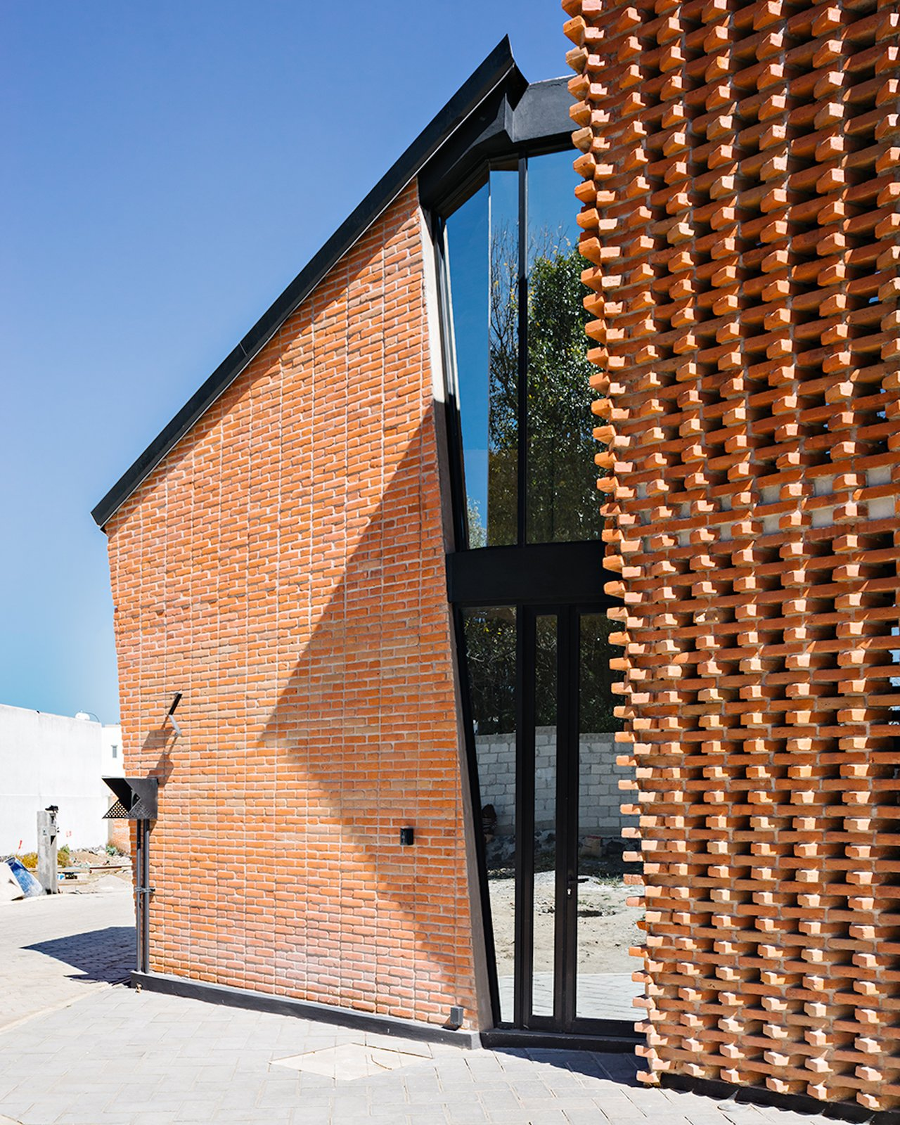 Exterior, Gable RoofLine, House Building Type, Brick Siding Material, and Metal Roof Material The entrance door is made of mirror-like glass to enhance privacy.    Photo 7 of 14 in Extruded Red Bricks Create a Gorgeous, Geometric Mexican Home