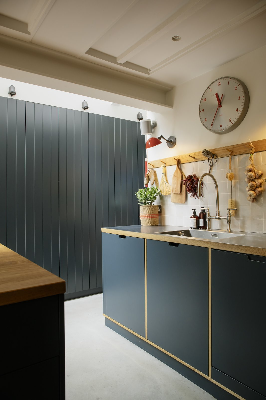 Kitchen, Recessed Lighting, Concrete Floor, Wall Lighting, Wood Counter, Metal Counter, Wood Cabinet, Drop In Sink, and Ceramic Tile Backsplashe The kitchen joinery is by Barnaby Reynolds.    Photo 8 of 14 in Before & After: A London Home Doubles as a Cheery Work Space
