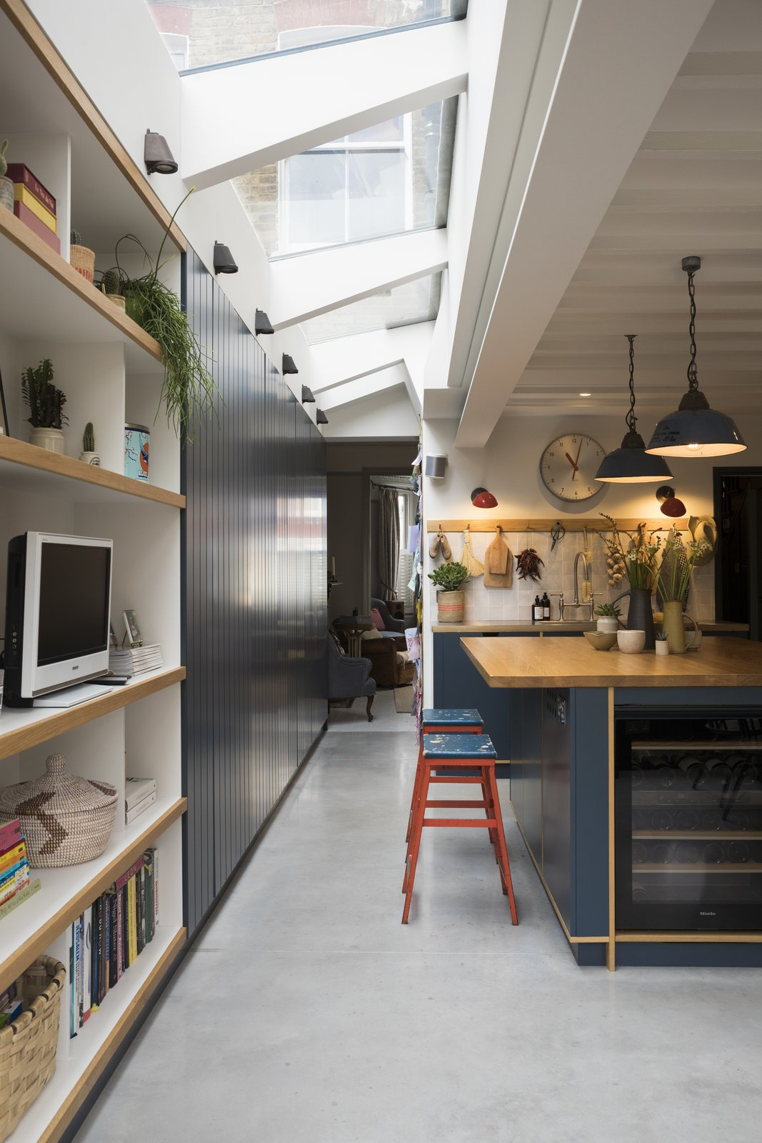 Kitchen, Concrete, Wine Cooler, Wood, Wall, Wood, Ceramic Tile, Drop In, and Pendant The expansive skylights are by Rooflight Architectural.    Best Kitchen Concrete Wood Wall Wine Cooler Photos from Before & After: A London Home Doubles as a Cheery Work Space