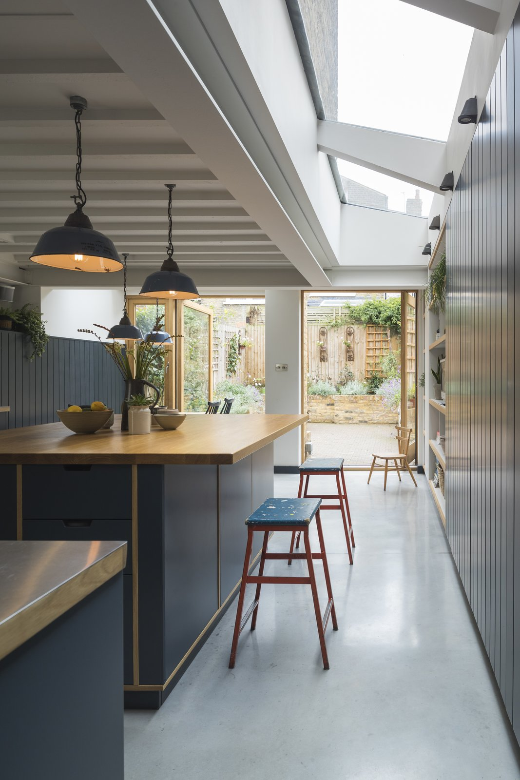 Kitchen, Wood Counter, Concrete Floor, Wood Cabinet, Pendant Lighting, and Ceiling Lighting Skylights dramatically brighten the kitchen.    Photo 6 of 14 in Before & After: A London Home Doubles as a Cheery Work Space