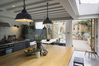 Expansive oak-framed pivot doors frame views of the rear garden, and also form a functional extension to the kitchen for dining, socializing, and play.