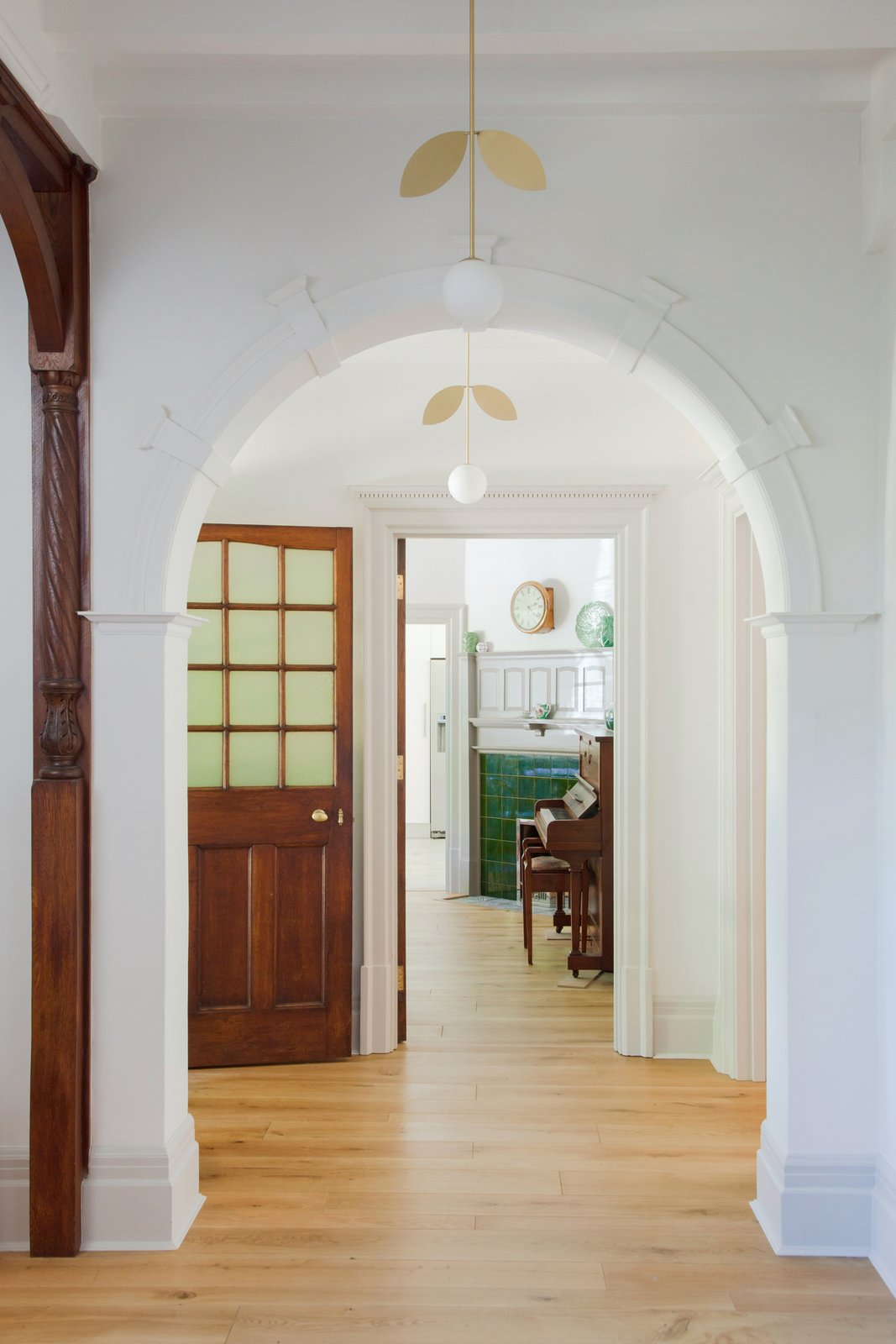 Hallway and Light Hardwood Floor The crisp, white walls contrasts beautifully with the warm, dark wood throughout the house. Here, the hallway lighting is by Areti.    Photo 9 of 16 in An English Arts and Crafts Home Becomes Delightfully Modernized