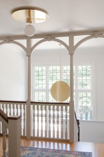 A Pinch pendant light hangs gracefully in the airy hall.