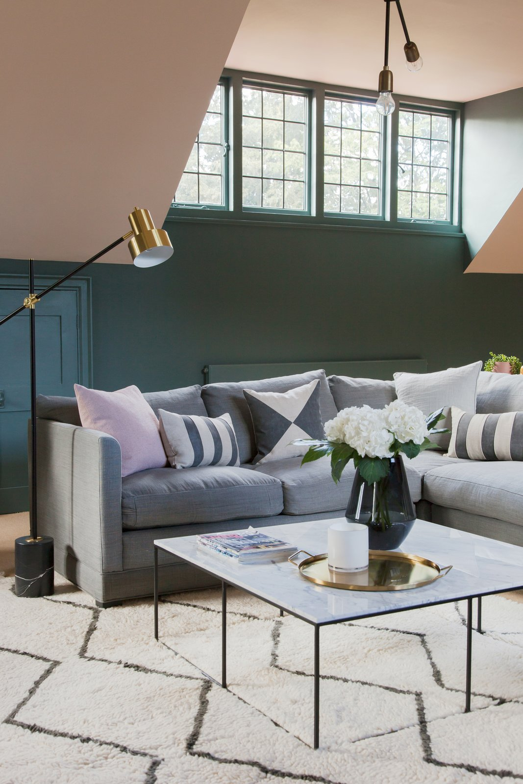 Living Room, Floor Lighting, Coffee Tables, Sofa, Pendant Lighting, and Rug Floor A peek at the inviting sitting area in the attic level.     Photo 6 of 16 in An English Arts and Crafts Home Becomes Delightfully Modernized