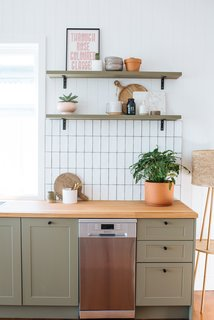 To unify the different living zones, they built DIY floating shelves with wood planks from Bunnings that they painted in the same shade of Haymes Paint as the cabinets.