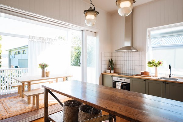 To unify the different living zones, the couple built DIY floating shelves with wood planks from Bunnings that they painted in the same shade of Haymes paint as the cabinets.