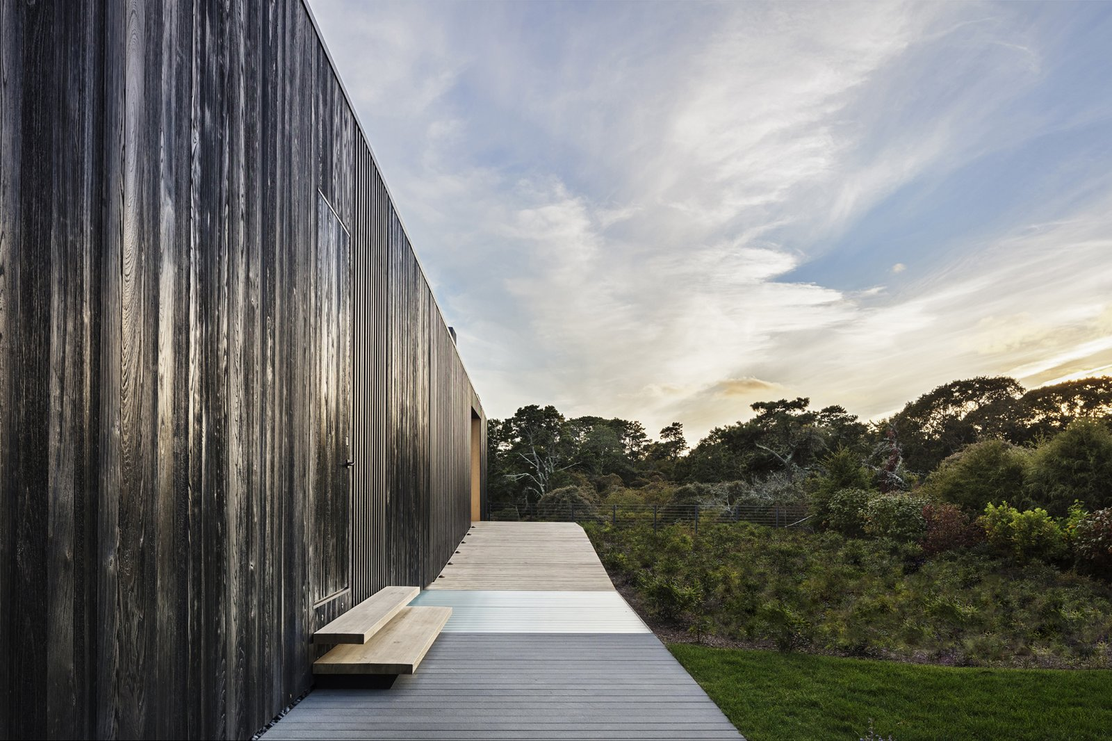 Outdoor, Hardscapes, Wood, Shrubs, Trees, Woodland, Horizontal, Wire, Grass, Large, Wood, and Vertical On the entry side, the house is a single-story long gable structure.  Best Outdoor Woodland Hardscapes Photos from A Student and Teacher Team Up on a Multi-Generational Martha's Vineyard Abode