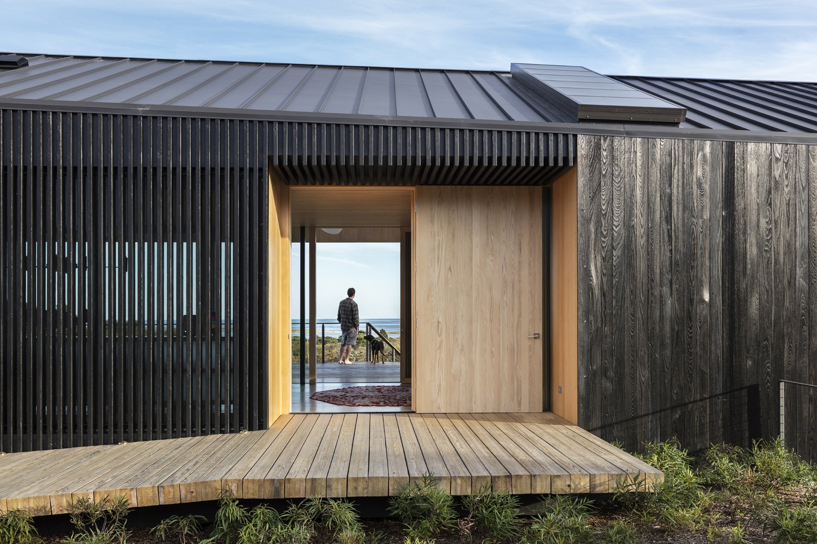 Outdoor, Small, Wood, Wood, Shrubs, Vertical, and Back Yard Aaron Schiller provided the shou sugi ban louvers that enclose the dining space and create privacy from the entry path.    Best Outdoor Small Vertical Photos from A Student and Teacher Team Up on a Multi-Generational Martha's Vineyard Abode