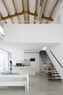Floating stairs in the dining area lead up to a mezzanine loft.
