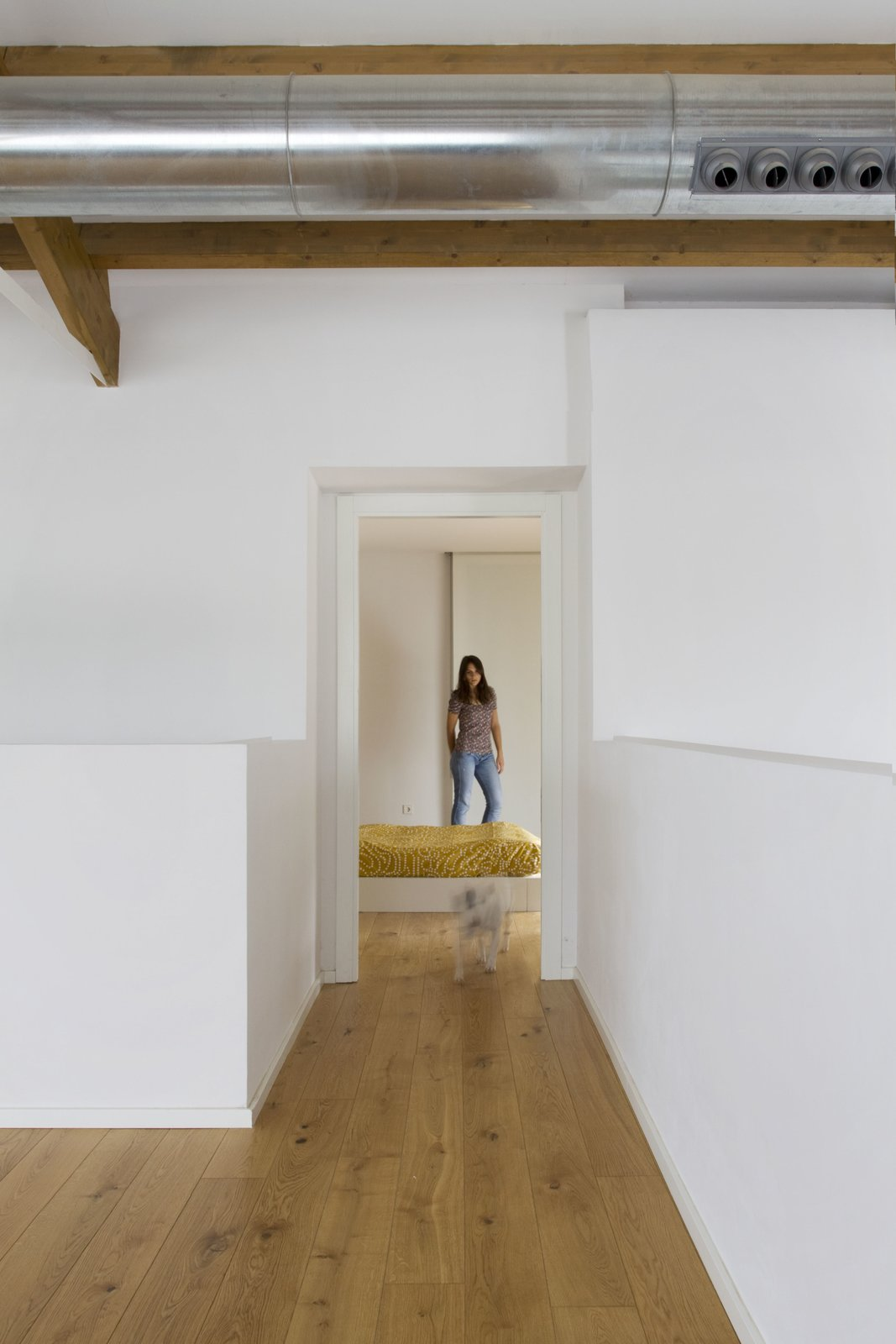 Bedroom, Medium Hardwood Floor, and Bed Polished cement was used for the common areas on the lower level, while wood was used for the more private mezzanine level to create a sense of warmth and intimacy.    Photo 9 of 11 in A Minimalist Mediterranean Home Rises in Rural Spain