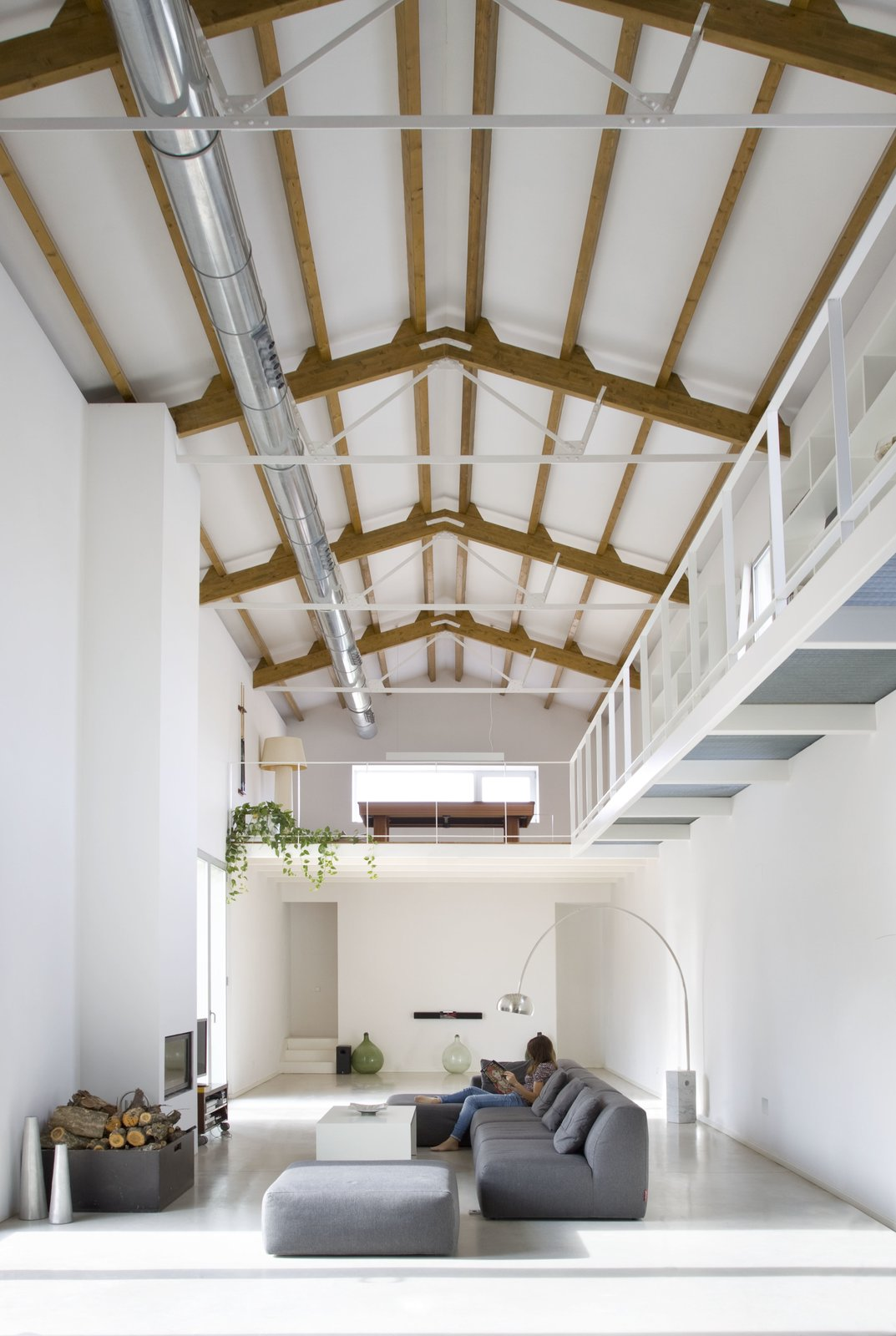 Living Room, Floor Lighting, Sofa, Standard Layout Fireplace, Concrete Floor, and Ottomans The wooden beams on the ceiling have been left exposed to add warmth and color to the otherwise simple white color scheme.    Photo 7 of 11 in A Minimalist Mediterranean Home Rises in Rural Spain