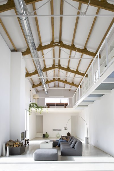 The wooden beams on the ceiling have been left exposed to add warmth and color to the otherwise simple white color scheme.