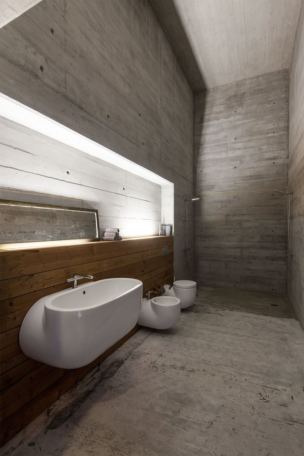 Bath, One Piece, Concrete, Wall Mount, Concrete, Recessed, Wood, and Open An industrial-inspired bathroom has fixtures that look like sections of cut pipes.  Best Bath Wood Recessed Photos from Two Ponds Bookend This Concrete-and-Wood Residence in Portugal