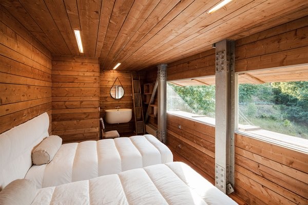 For small bedroom ceiling lighting ideas, let natural light take the lead. This peaceful bedroom does just that, and adds hints of light by incorporating strips of light into the woodwork of the ceiling.