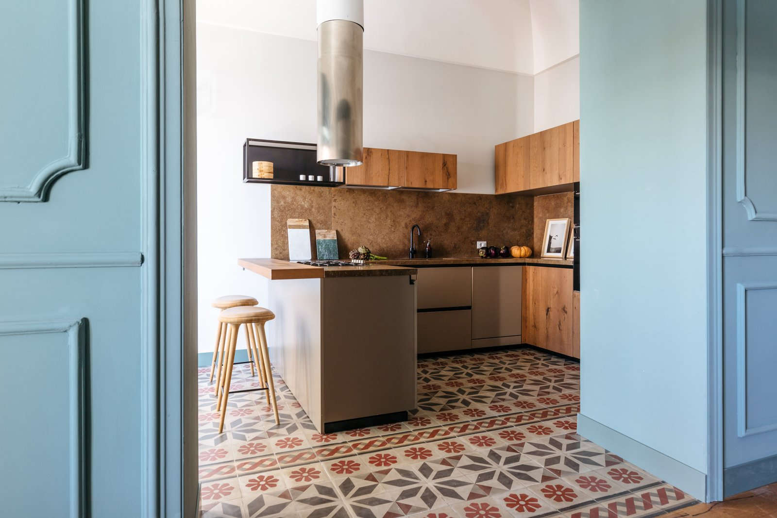 Kitchen, Cooktops, Cement Tile, Marble, Wood, Wood, Accent, Marble, Range Hood, Ceramic Tile, and Undermount Wooden and marble cutting boards by Kaat Collection.  Best Kitchen Undermount Accent Cooktops Photos from A Renovated Apartment in an 18th-Century Sicilian Building Pays Homage to the Sea