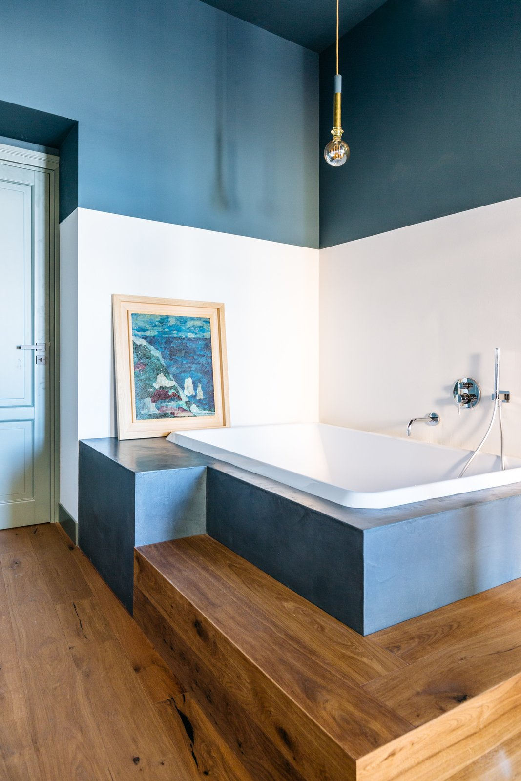 Bath, Medium Hardwood, Soaking, Pendant, and Undermount A beautifully renovated apartment in the capital of Sicily echoes the colors  and textures of the sea. The bathroom in particular evokes water, with textured tadelakt cement and Wet System Wall & Deco wallpaper.  Bath Undermount Medium Hardwood Soaking Photos from A Renovated Apartment in an 18th-Century Sicilian Building Pays Homage to the Sea