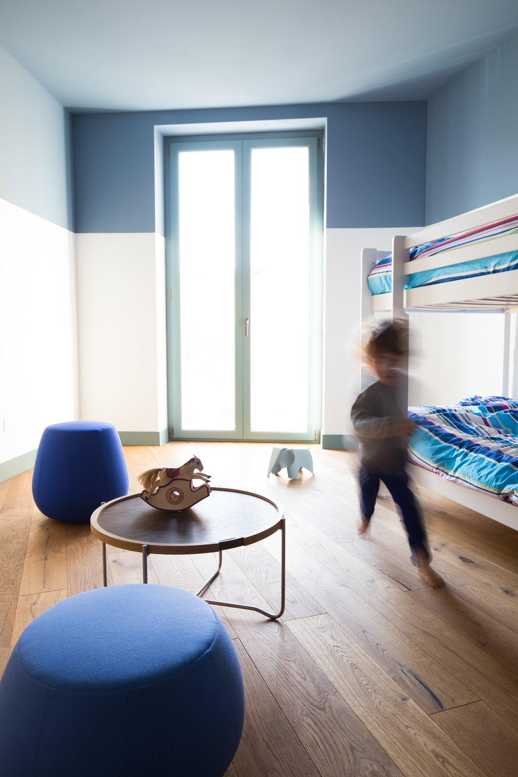 Kids, Bunks, Bedroom, Medium Hardwood, Toddler, Neutral, Chair, and Night Stands The children's bedroom with bunk beds.  Best Kids Toddler Medium Hardwood Photos from A Renovated Apartment in an 18th-Century Sicilian Building Pays Homage to the Sea