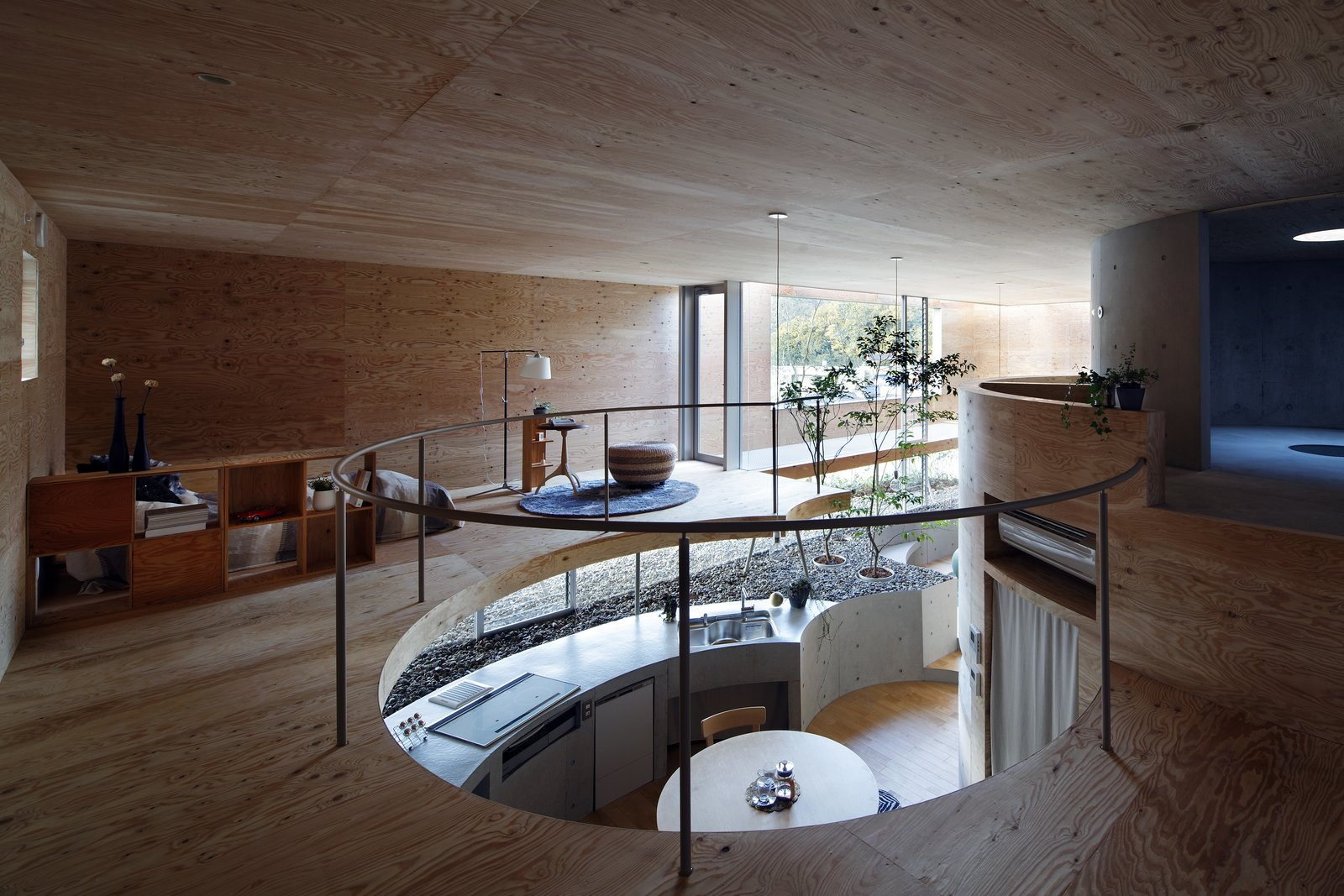Living Room, Pendant Lighting, Recessed Lighting, Light Hardwood Floor, Lamps, End Tables, Rug Floor, Shelves, and Stools The circular kitchen and dining area feels like part of the garden.  Photo 9 of 12 in This Japanese Home Has a Sunken Interior That Blends Into the Earth