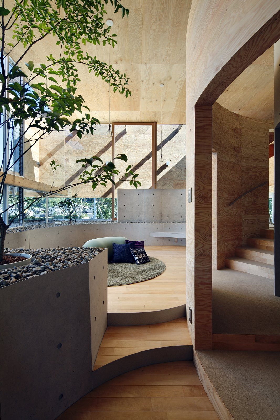 Living, Bench, Light Hardwood, Pendant, Rug, and Stools Indoor plants and rocks create a strong visual connection to the outdoors.  Best Living Bench Stools Photos from This Japanese Home Has a Sunken Interior That Blends Into the Earth