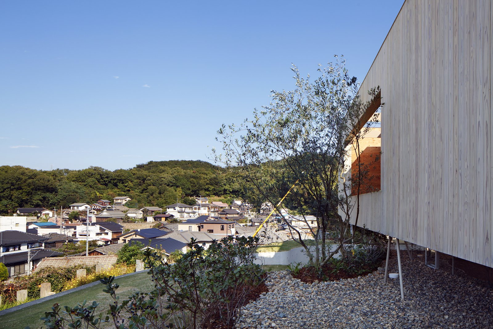 Exterior, Flat RoofLine, House Building Type, and Wood Siding Material The house is located on a terraced hill in Okayama Prefecture near the Seto Inland Sea in Japan.  Photo 5 of 12 in This Japanese Home Has a Sunken Interior That Blends Into the Earth
