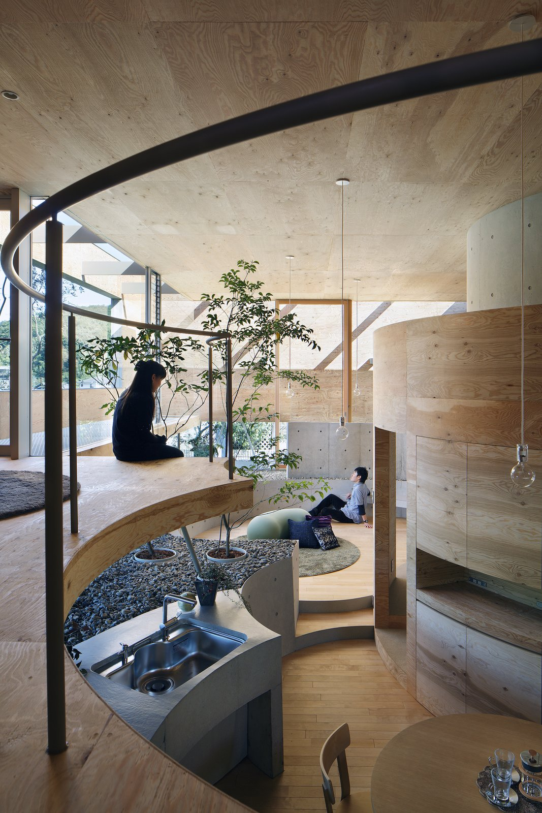 Living Room, Table, Pendant Lighting, Light Hardwood Floor, Rug Floor, Chair, and Stools A doorless sleeping space is located within the mezzanine level.  Photo 7 of 12 in This Japanese Home Has a Sunken Interior That Blends Into the Earth