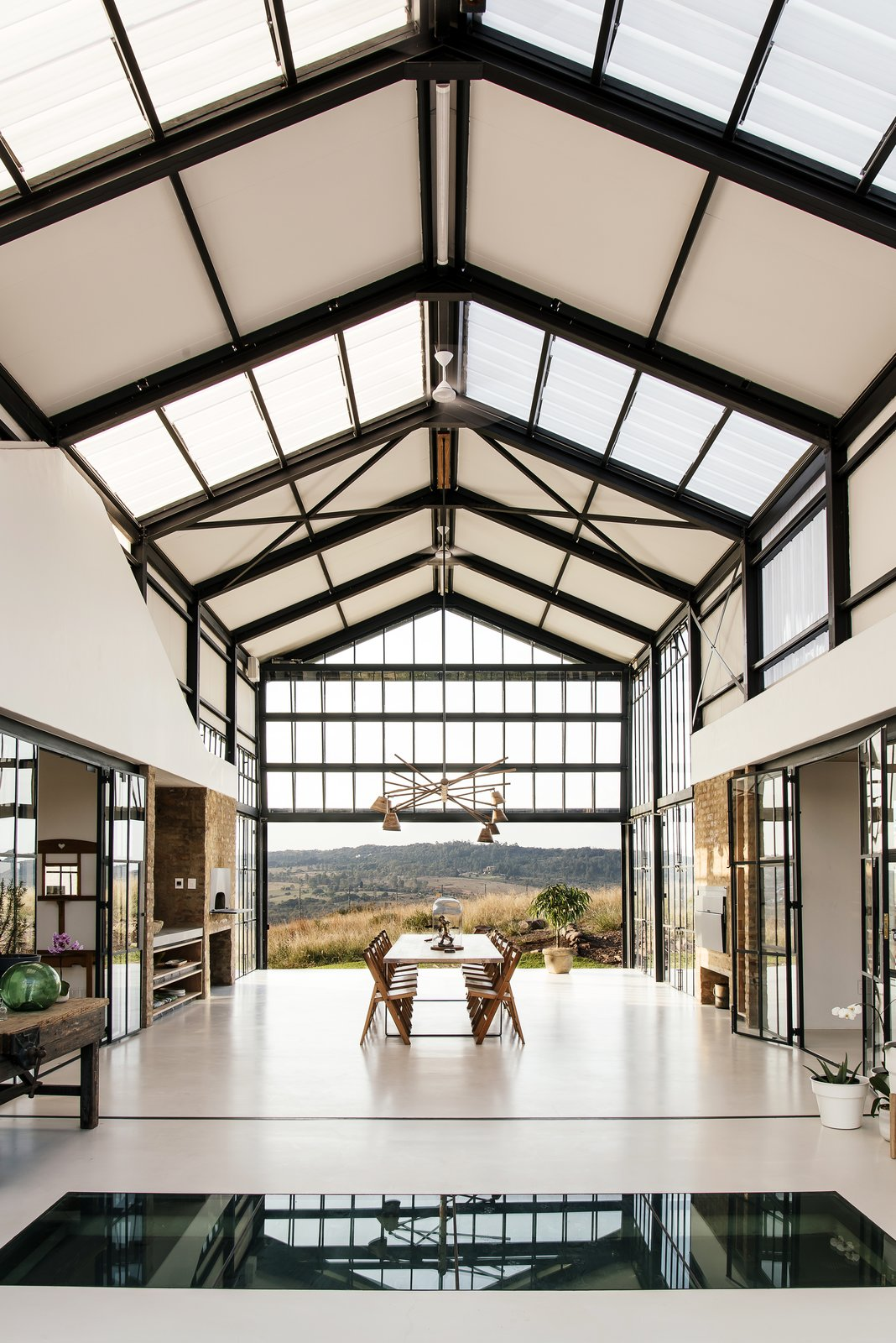Dining, Table, Pendant, Concrete, Chair, Storage, Ceiling, and Shelves The wine cellar can be seen through the glass section of the floor.  Dining Concrete Table Ceiling Shelves Photos from A South African Architect Designs an Off-Grid, Modern Home For Her Parents