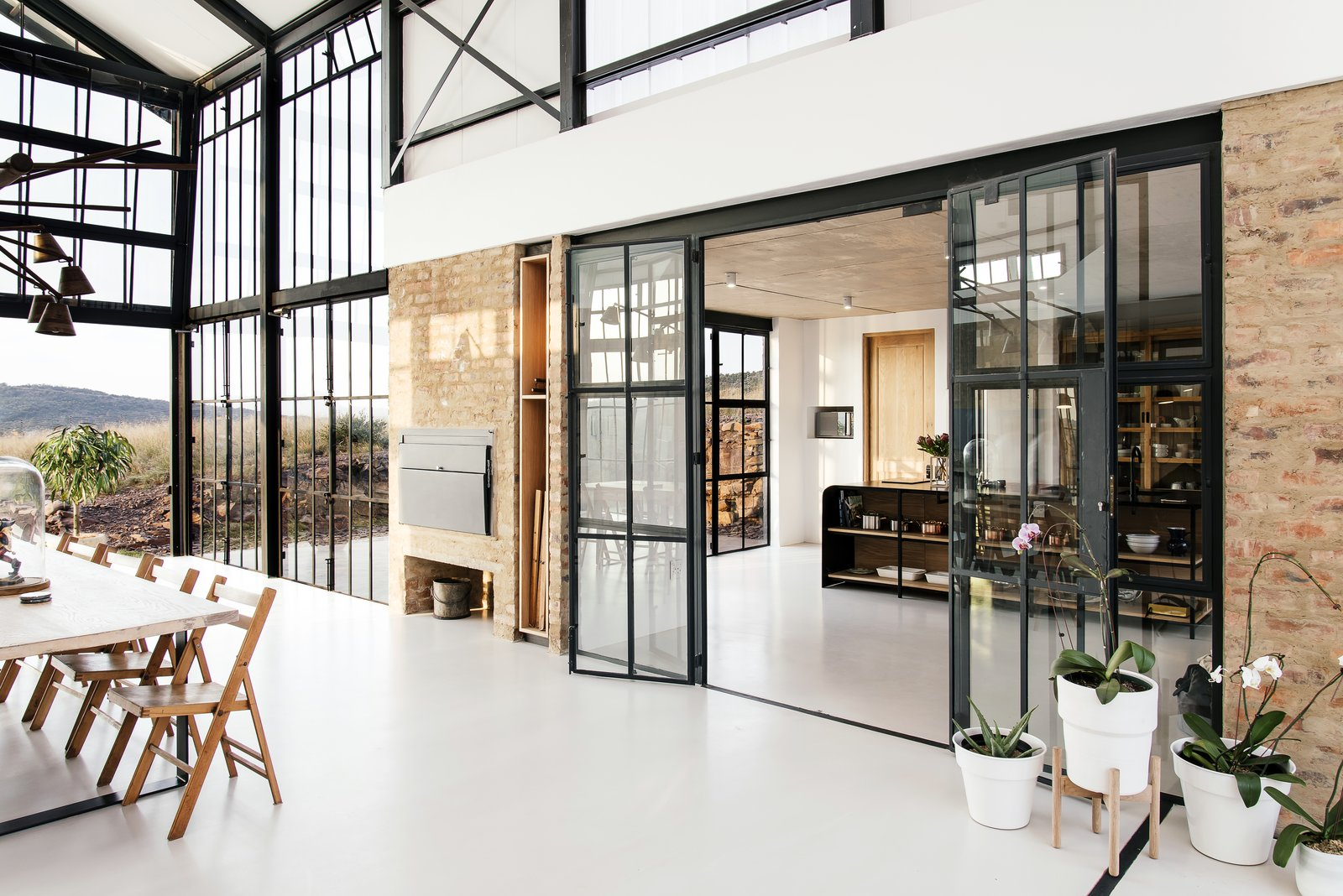 Dining, Concrete, Table, Pendant, Accent, Chair, and Ceiling The dining room connects to the kitchen.  Best Dining Accent Ceiling Pendant Photos from A South African Architect Designs an Off-Grid, Modern Home For Her Parents