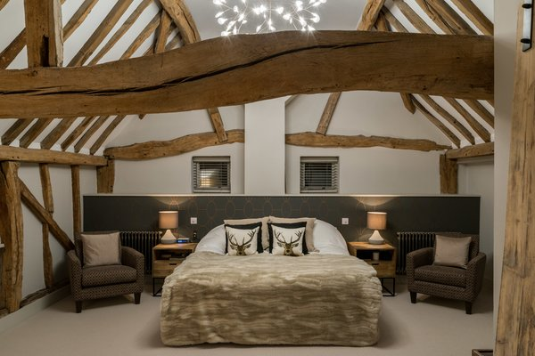 Master bedroom lighting ideas for a vaulted ceiling include adding a dramatic statement piece, like this stunning Moooi Heracleum pendant light.