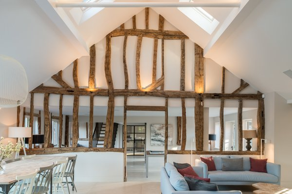 The design team restored the existing wood beams, giving nod to the home's former rustic life, while introducing big windows, white walls, and clean lines.