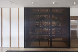 "The new kitchen features a ""super pantry"" concealed behind sleek, black, screen-like sliding doors."