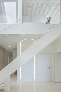 A modern white staircase connects the two levels.