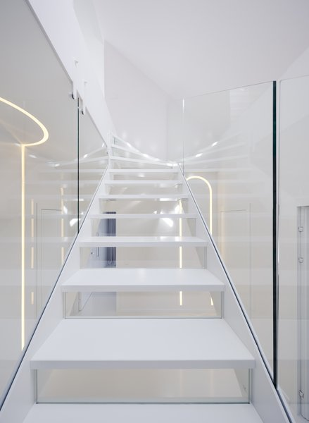 A hanging steel structure makes the stairs visually lightweight, while glass railings reflect natural and artificial light.